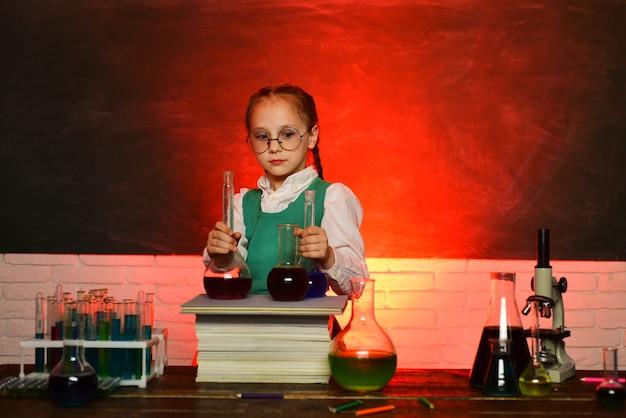 学校に戻る。小学校の子供。背景に黒板を持つ教室の子供。私の化学実験。化学のデモンストレーション。