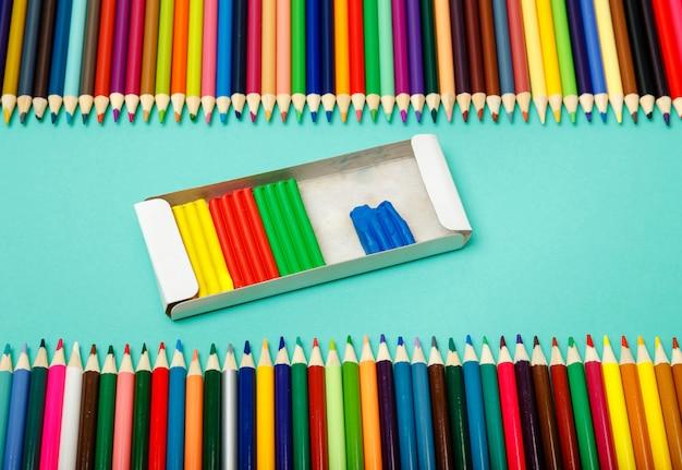 Обратно в школу. цветные карандаши и лепка из глины на синем фоне