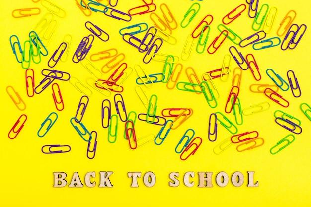 Обратно в школу. цветные скрепки на желтом фоне случайным образом и фраза деревянными буквами