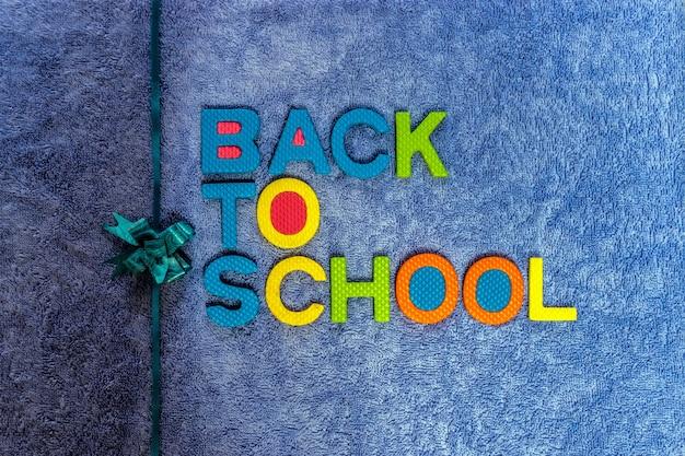 Обратно в школу. красочный пробковый материал с красивыми лентами и синим тканевым фоном