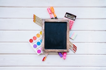 Back to school composition with slate on wooden background