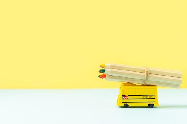 黄色いスクールバスと木製の鉛筆で学校に戻る構成