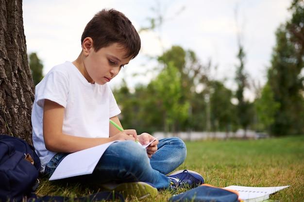 学校のコンセプトに戻ります。愛らしい賢い思春期前の小学生、宿題をしているハンサムな男の子、ワークブックに書いている、都市公園の緑の芝生に座っている。学校での最初の日の後の美しい子供