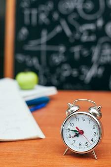 Обратно в школу концепции, будильник на школьной доске, университет, колледж