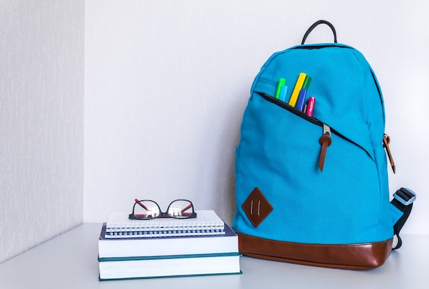 Снова в школу концепции. рюкзак со школьными принадлежностями. копировать пространство