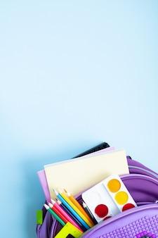 学校のコンセプトに戻ります。青の背景に学用品が入ったバックパック。上面図。コピースペース