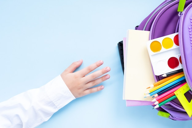学校のコンセプトに戻ります。青い背景に学用品が入ったバックパック。上面図。 web用の長いフォーマット