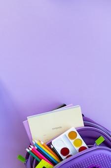学校のコンセプトに戻ります。紫色の背景に学用品が入ったバックパック。上面図。コピースペース