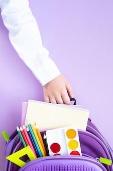 学校のコンセプトに戻ります。紫色の表面に学用品が入ったバックパック。シャツを着た1年生の手がバックパックを持っています。ストーリーの垂直フォーマット