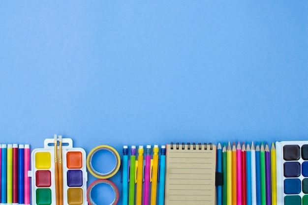 Снова в школу концепции баннера. канцелярские товары выложены в ряд на голубом фоне. образование. вид сверху. копировать пространство