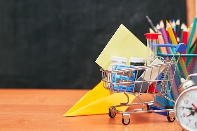 Снова в школу, корзина с канцелярскими принадлежностями на школьной доске, университет, колледж, копировальное пространство, крупный план