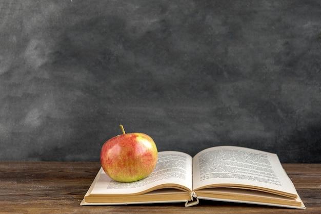 Снова в школу концепции. книга и цветы астра на черной доске. 1 сентября день.