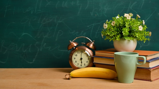 학교 개념으로 돌아가기. 책, 빈티지 알람 시계, 바나나, 머그, 식물, 녹색 칠판 위의 나무 탁자 위에 있는 모형 공간
