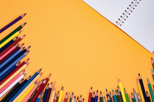 学校概念に戻る。オレンジ色の背景に色鉛筆と教育装置。