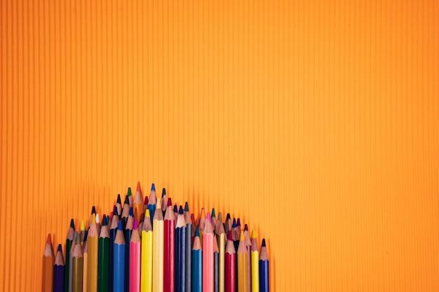 学校概念に戻る。オレンジ色の背景に色鉛筆。
