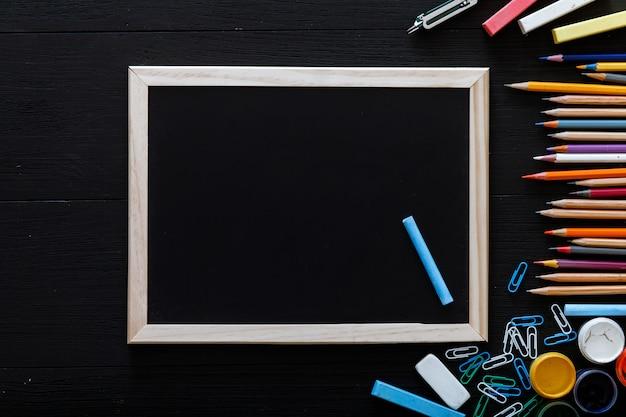 Вернуться к концепции школы, творческое рабочее пространство с красочными карандашами, красками, рамкой и другими школьными принадлежностями для школьных занятий на черном столе, время учиться, современное начальное образование, вид сверху, копирование пространства