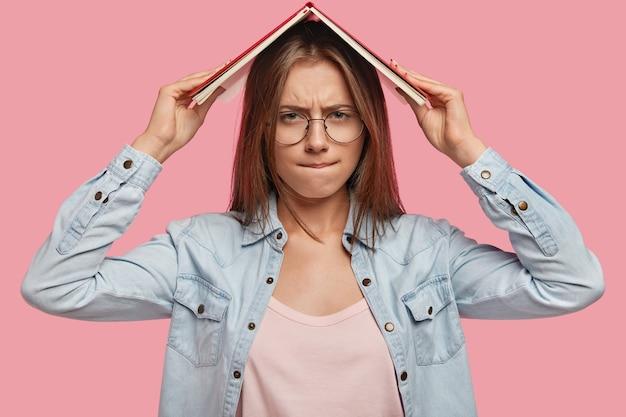 学校のコンセプトに戻る。不機嫌な女子学生は頭上に本を持って、不満な表情をしていて、試験のために詰め込みたくない、ファッショナブルなデニムジャケットを着て、ピンクの壁に隔離されています