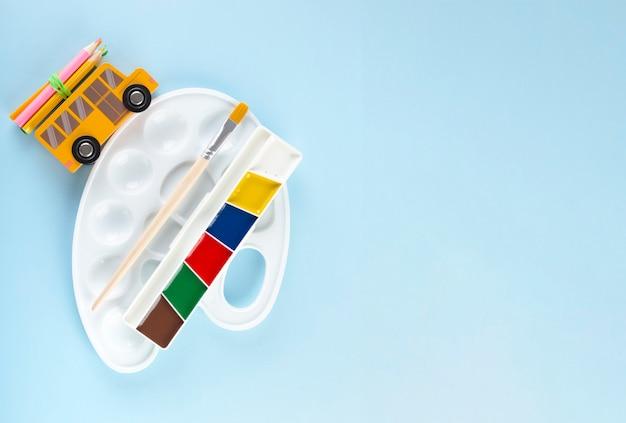 Снова в школу концепции. принадлежности для рисования. палитра приводов школьного автобуса игрушки, на синем фоне. вид сверху. копировать пространство