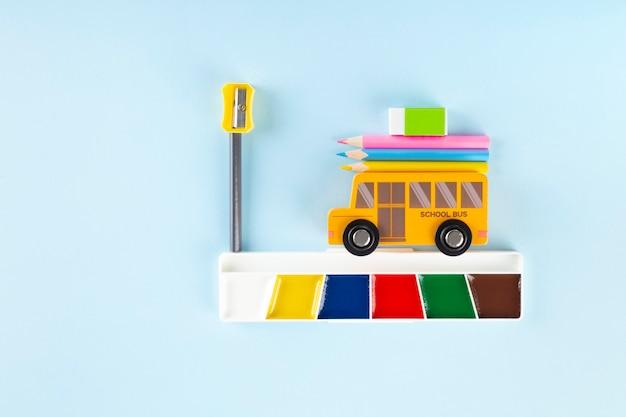 다시 학교 개념. 드로잉 액세서리. 장난감 학교 버스 파란색 배경에 수채화를 드라이브. 평면도. 공간 복사