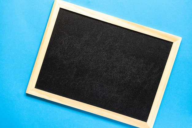 学校のコンセプトに戻るテキスト用の空の黒板フラットレイ学校の黒い黒板が光に傾いている
