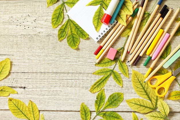 Обратно в школу концепции flatlay фон стол с осенними листьями и различными школьными принадлежностями