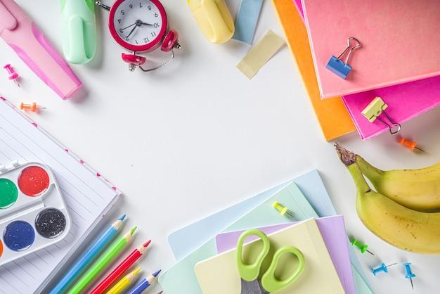 학교 개념으로 돌아가기. 다양한 학교 사무용품과 문구류가 있는 흰색 배경에 플랫레이, 상위 뷰 복사 공간