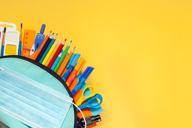 Снова в школу концепции. полный синий школьный рюкзак с различными принадлежностями на желтом фоне. плоская планировка.