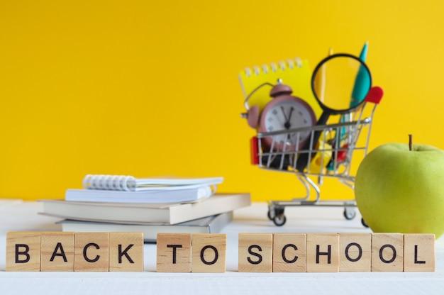 学校のコンセプトに戻る学用品が入った食料品のカートグリーンアップルのメモ帳とテーブルの上の本