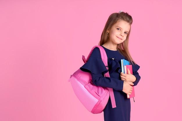 学校に戻るコンセプト学校の制服ドレスピンクの明るいバックパックを身に着けているコピーブックノートブックを持つ素敵な自信を持って美しい賢い女の子の半分回転した写真の肖像画が分離されました