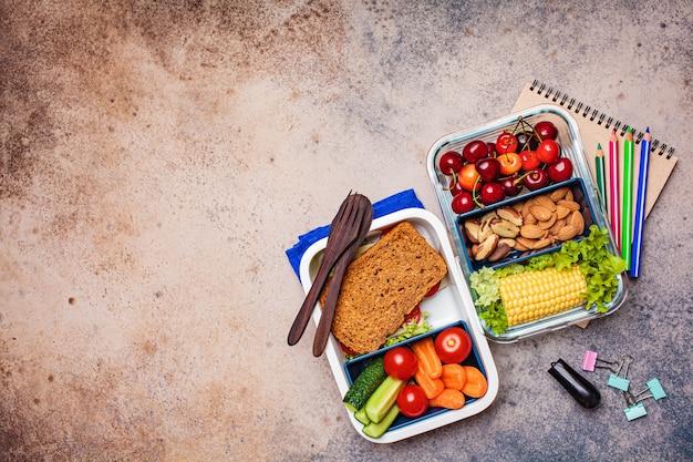 다시 학교 개념. 건강하고 신선한 음식이 담긴 도시락. 샌드위치, 야채, 과일 및 견과류 식품 용기, 어두운 배경.