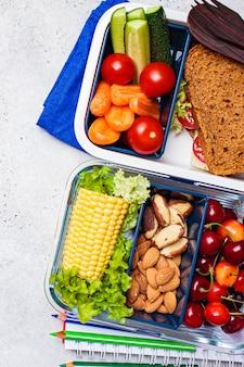 学校のコンセプトに戻る。ヘルシーな生鮮食品のお弁当。サンドイッチ、野菜、果物、ナッツ、食品容器、明るい背景。