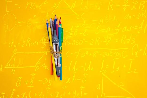 수학 공식을 사용하여 노란색 배경에 도구 및 복사 공간이 있는 학교 개념으로 돌아가기