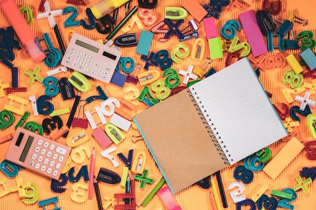 学校概念に戻る。オレンジの背景にノートブックと教育機器。