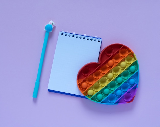 Снова в школу концепции. блокнот, синяя ручка и игрушка-антистресс в виде сердечка на розовом фоне. вид сверху. квартира лежала с копией пространства.