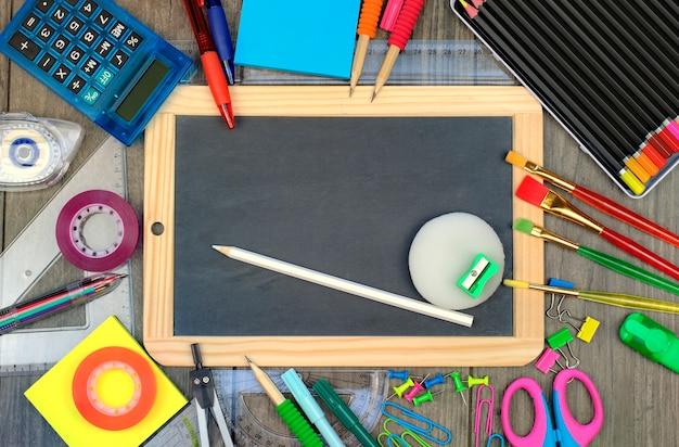 Снова в школу: офисные и школьные принадлежности с доской на деревянном фоне