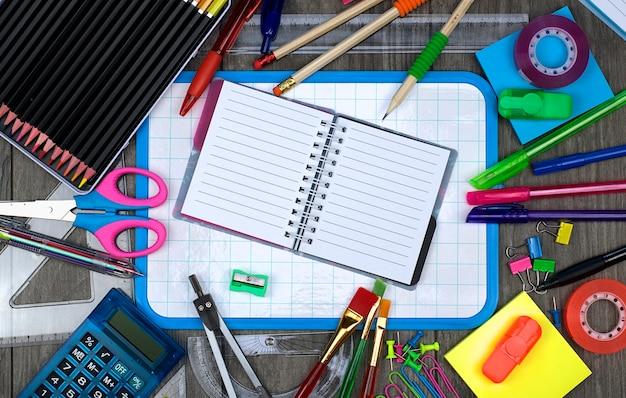 Снова в школу: офисные и школьные принадлежности с записной книжкой на деревянном фоне