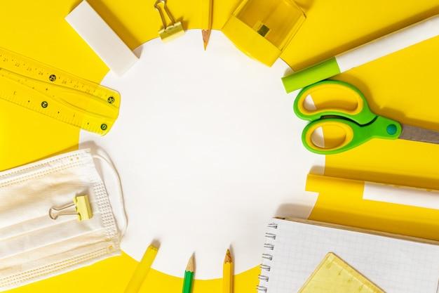 Обратно в школу концепции. канцелярские товары в круг с местом для текста. ножницы, фломастеры, точилка, защитная медицинская маска, линейка, блокнот расположены по кругу