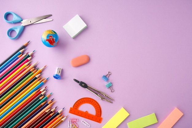 Обратно в школу концепции на фоне текстуры фиолетовый бумаги.