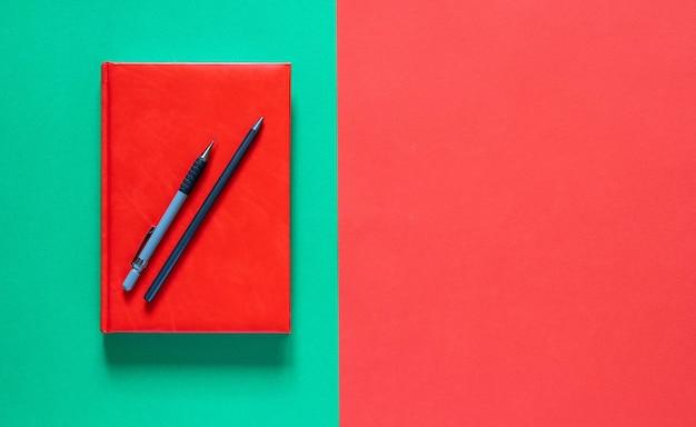 学校のコンセプトに戻ります。鉛筆で赤いメモ帳。緑と赤の背景。コピースペースのあるフラットレイ。秋