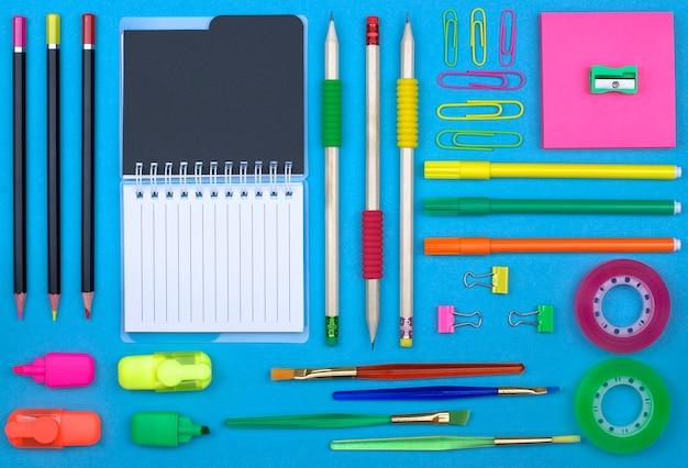Вернуться к концепции школы: школьные и офисные принадлежности на фоне синей бумаги.
