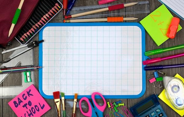 Обратно к концепции школы: школьные и офисные предметы с белой доской на деревянном фоне