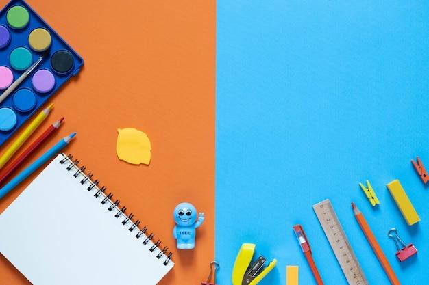 学校のコンセプトに戻ります。オフィステーブルの学用品や事務用品。 2色の背景。コピースペースのあるフラットレイ。秋