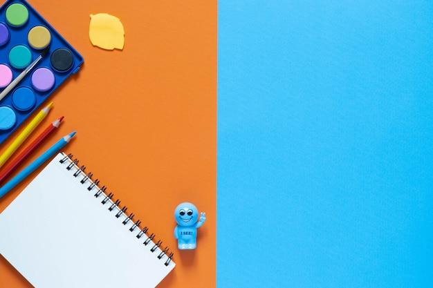 学校のコンセプトに戻ります。オフィステーブルの学用品や事務用品。 2色の背景。コピースペース付きのフラットレイ。