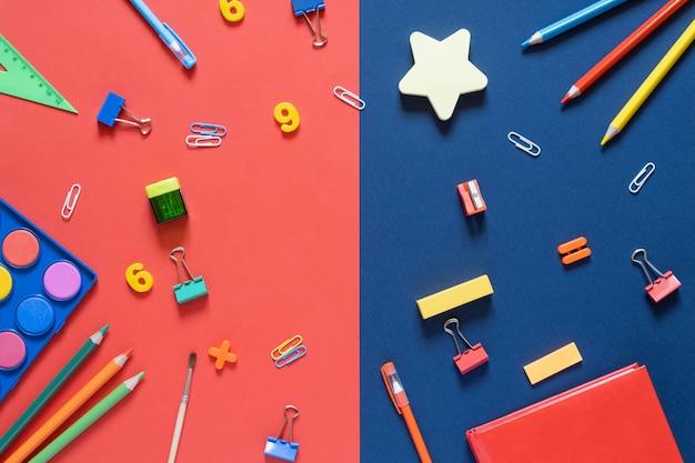 学校のコンセプトに戻ります。オフィステーブルの学用品や事務用品。青と赤。コピースペースのあるフラットレイ。秋