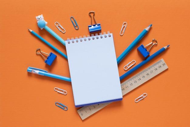 学校のコンセプトに戻ります。オフィステーブルの学用品や事務用品。オレンジ色の背景。コピースペースのあるフラットレイ。秋