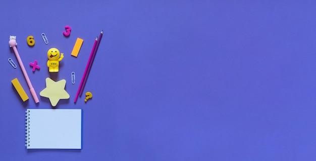 学校のコンセプトに戻ります。オフィステーブルの学用品や事務用品。紫の背景。コピースペースのあるフラットレイ。秋