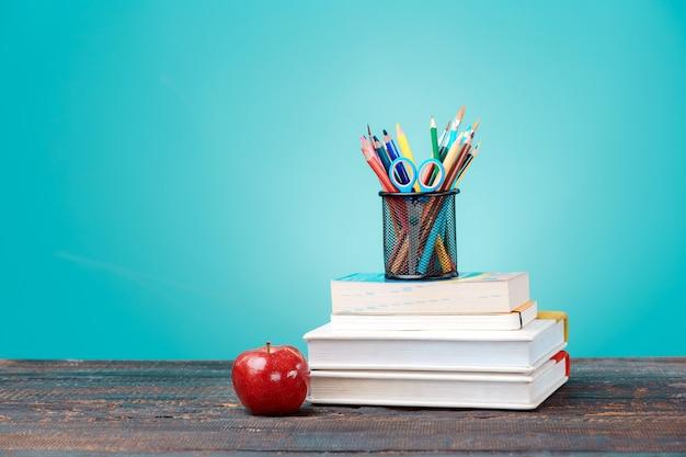 学校に戻るコンセプト。学校の本、色鉛筆、青い壁にリンゴ