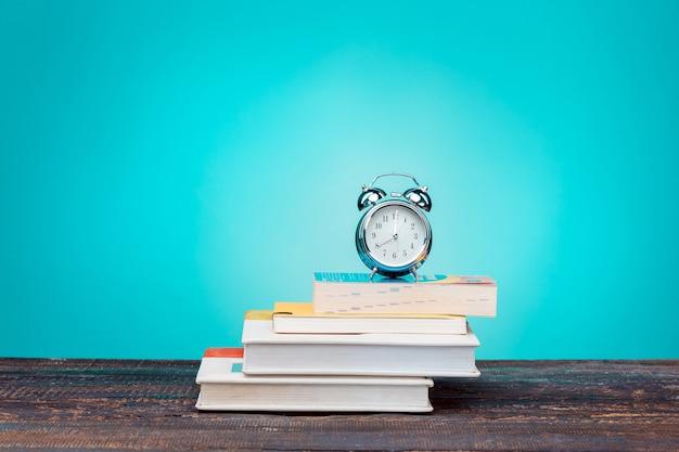 学校に戻るコンセプト。学校の本、色鉛筆、青い壁の時計