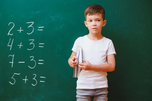 学校のコンセプトに戻ります。クラスの学童。緑の黒板に対して幸せな子供。教室の賢い子供。アイデアと教育の概念