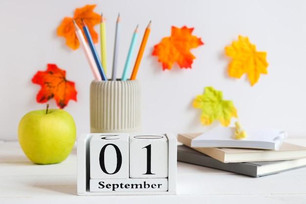 Снова в школу концепция школьные канцелярские принадлежности зеленое яблоко и календарь от 1 сентября на столе